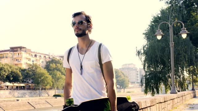 Man with longboard walking video
