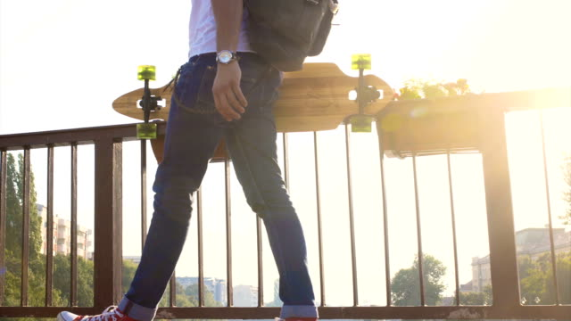 Man with longboard walking video