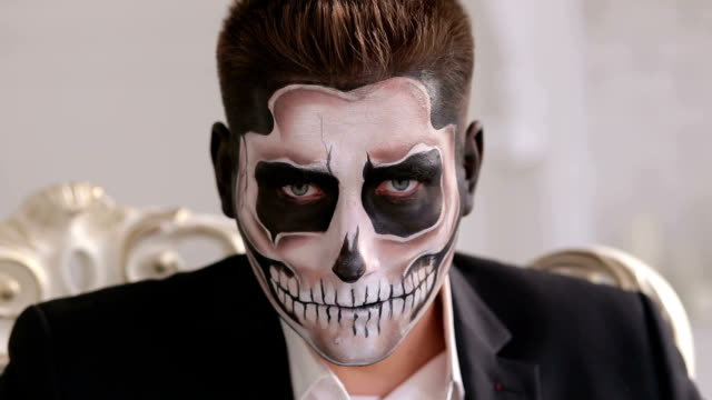 Man with make-up skeleton sitting in old grey chair. Halloween or horror theme.