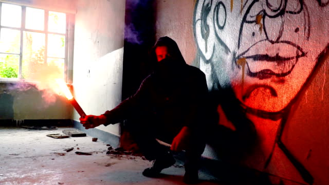 Man With Mask And Hoodie Crouching While Holding Flare