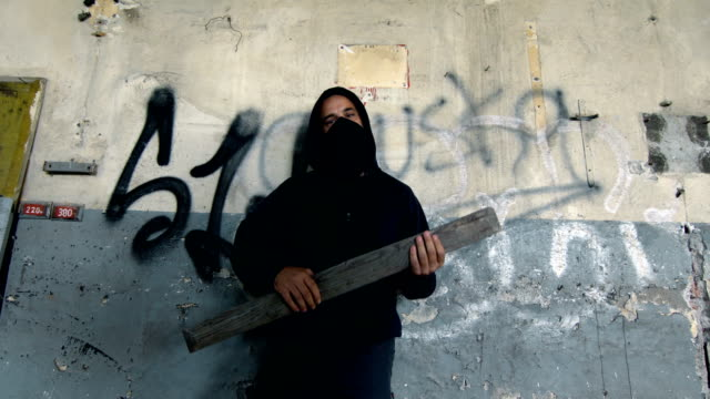 Man With Mask And Hoodie Holding A Plank