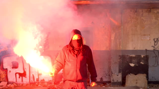 Man With Mask And Hoodie Holding Flare Walking Towards The Camera
