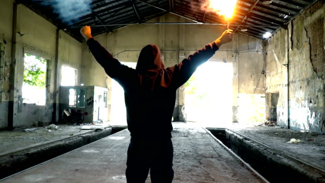 Man With Mask And Hoodie Holding Flare With Fist In The Air