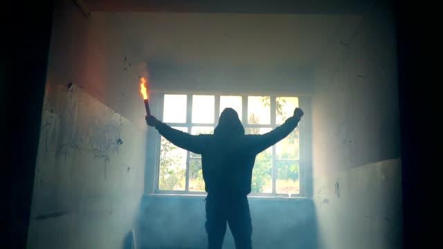 mann mit maske und hoodie halten flare mit faust in der luft - verbrecher stock-videos und b-roll-filmmaterial