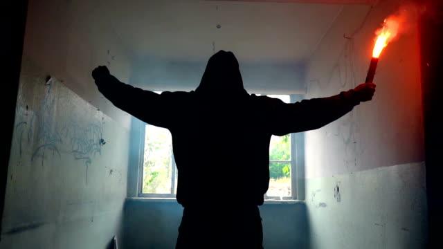 stockvideo's en b-roll-footage met man met masker en hoodie holding flare met vuist in de lucht - street style