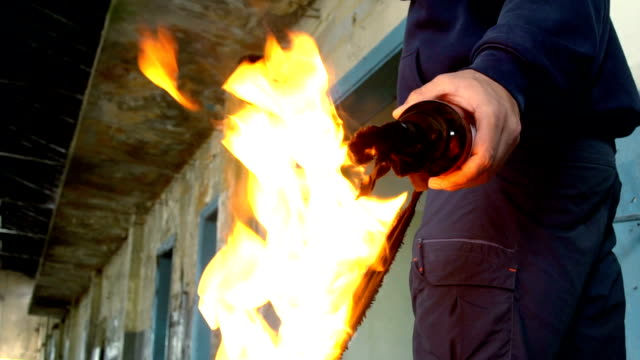 man with mask and hoodie holding molotov cocktail - close up - incendio doloso video stock e b–roll