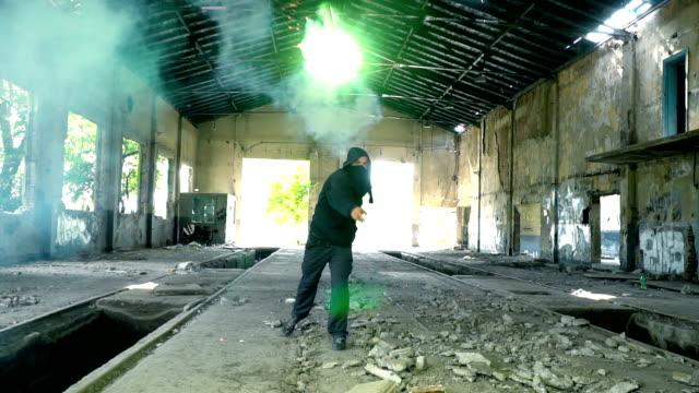 stockvideo's en b-roll-footage met man met masker en hoodie gooien flare naar de camera - street style