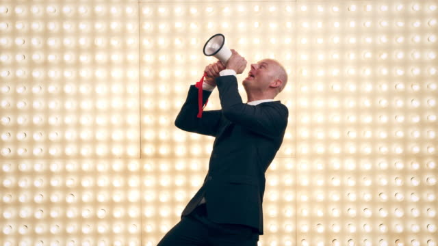 Man with megaphone in front of lightwall Selected Takes - Shot on RED Epic megaphone stock videos & royalty-free footage