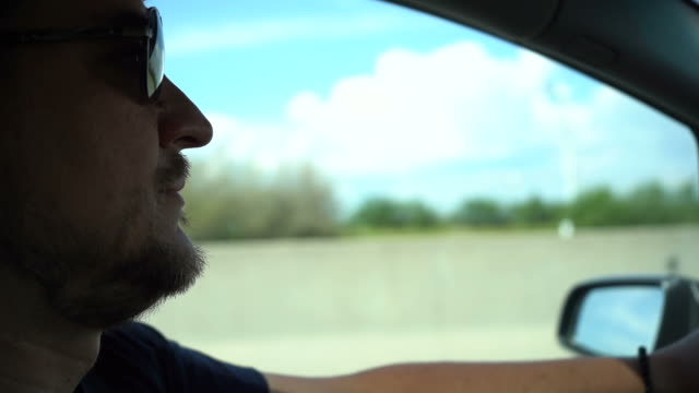 Man with messy beard and sunglasses driving car