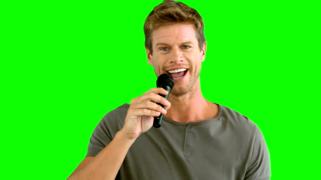 Man with microphone singing on green screen video