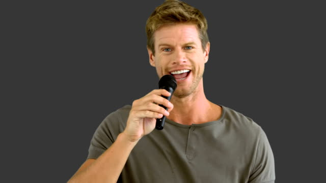 Man with microphone singing on grey screen video