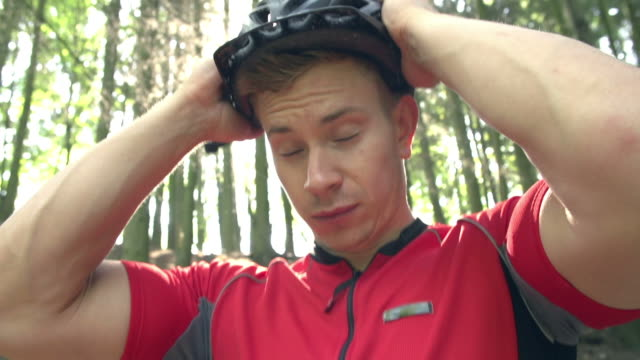 Man With Mountain Bike Fastening Safety Helmet In Forest video