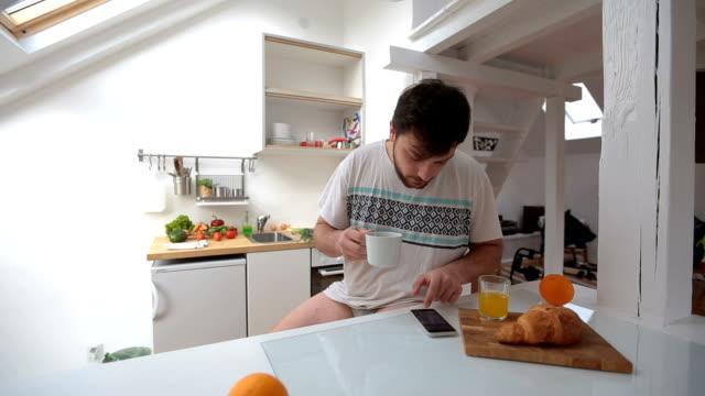 vidéos et rushes de homme avec aucun pantalon ayant une routine du matin avec café et smartphone - homme slip