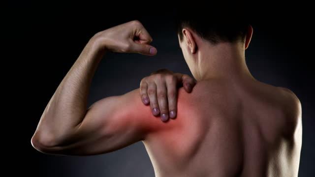 Hombre con dolor en hombro en fondo negro - vídeo