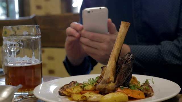 Man with phone making photo of a served dish video