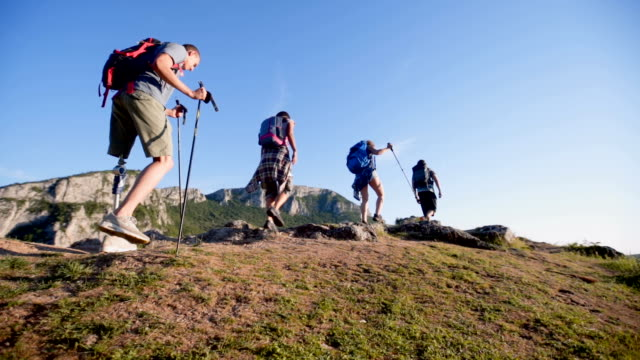Man with prosthetic leg hiking with friends in the mountain Group of people going to hiking. They exploring nature, camping and make camping fire. There is also a one man with artifical limb artificial limb stock videos & royalty-free footage