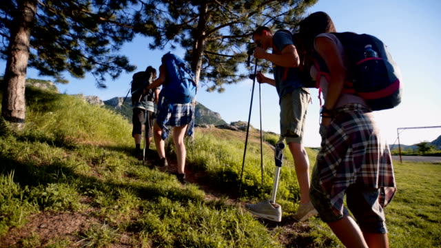 Man with prosthetic leg hiking with friends Group of people going to hiking. They exploring nature, camping and make camping fire. There is also a one man with artifical limb amputee stock videos & royalty-free footage