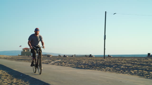 Man with prosthetic leg riding a bike at the beach video