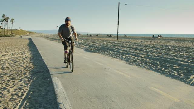 mannen med protetiska ridning cykel mot kameran - endast en man i 30 årsåldern bildbanksvideor och videomaterial från bakom kulisserna