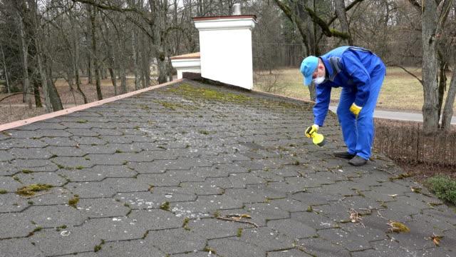 vidéos et rushes de homme avec des vêtements de protection et mousse de pulvérisation respirateur avec des produits chimiques sur le toit. - herbicide