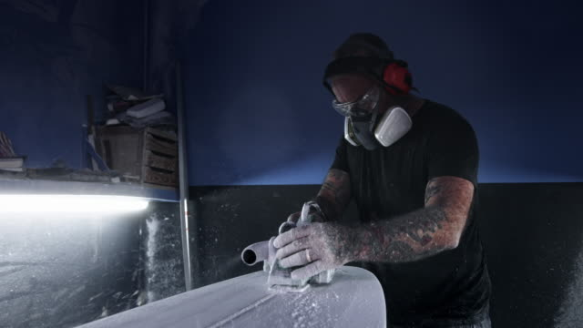 man with protective gear shaping surfboard with electrical sander - poliuretano polimero video stock e b–roll