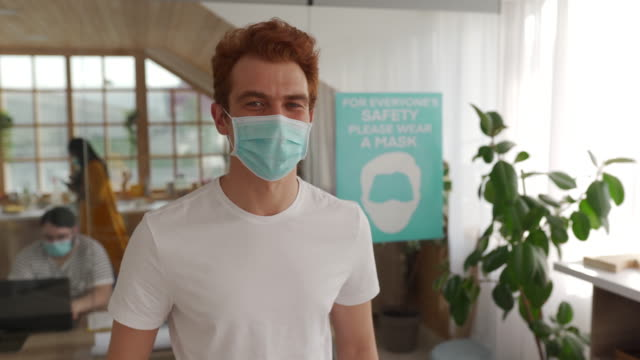 Man with protective mask standing in office video