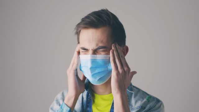 man med skyddande medicinsk mask gnugga tempel. studio porträtt av unga stilig kille med svår huvudvärk. hälso- och sjukvård, överarbete, stress, spänning - människohuvud bildbanksvideor och videomaterial från bakom kulisserna
