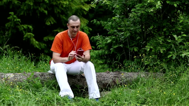Man with red smartphone sits on a fallen tree in the forest Adult man in orange t-shirt with red smartphone sits on a fallen tree in the forest. Man with smartphone and earphones. Male with cell phone one man only stock videos & royalty-free footage