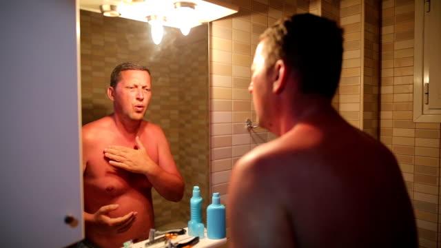 Homme à la peau rougie, démangeaison après coup de soleil - Vidéo