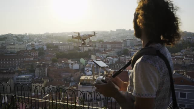 man with remote control using drone flying above roofs of buildings - azionare video stock e b–roll