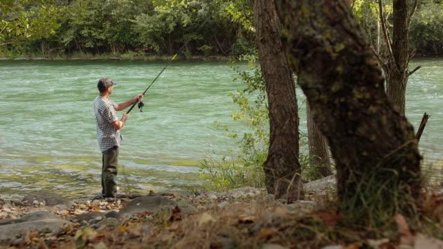 man with rod fishing trout on river in italy - bir orta yetişkin erkek sadece stok videoları ve detay görüntü çekimi