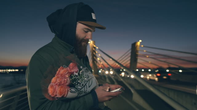 MS Man with rose bouquet using smart phone on bridge at dusk