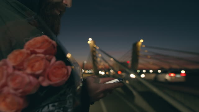 CU Man with rose bouquet using smart phone,texting on bridge at dusk
