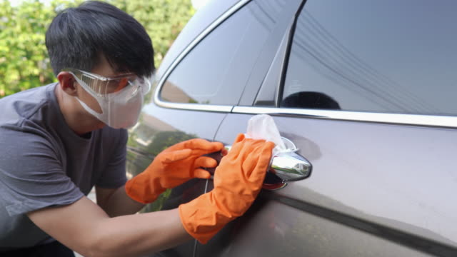 a man with safety glasses and face mask with hand glove wiping down door handle surfaces of car cleaning covid-19 virus at home. - hand on glass covid video stock e b–roll