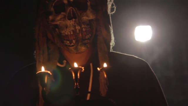 vidéos et rushes de homme avec le masque effrayant d'halloween retenant des bougies arrière éclairée par la lumière. rituel magique noir ou halloween effrayant rite - charmeur