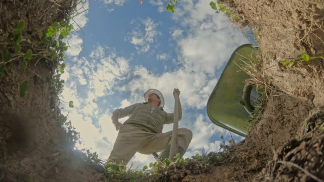MS Man with shovel filling hole to plant fruit tree