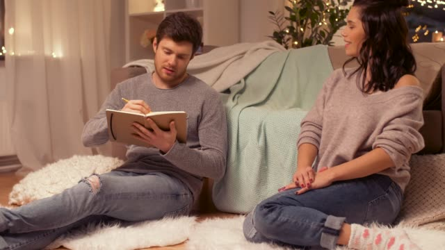 vídeos de stock e filmes b-roll de man with sketchbook drawing his girlfriend at home - hygge