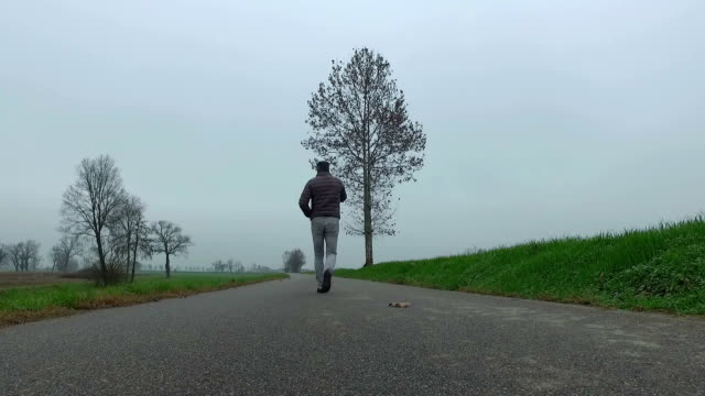Man with smart phone walking on country road video