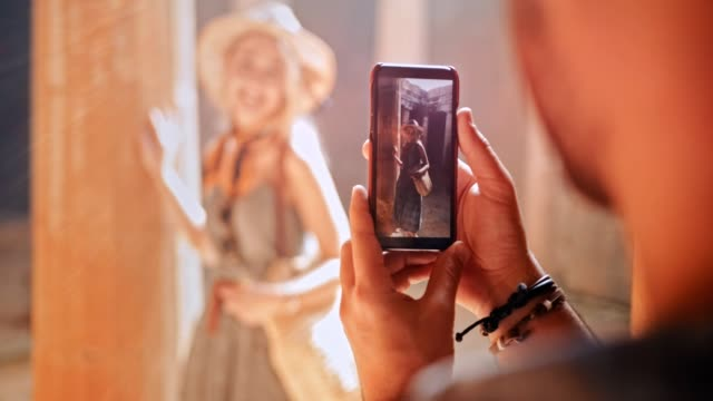 Man with smartphone taking photos of woman at ancient monument Man with mobile phone taking photos of girlfriend at ancient Greek archaeological site in summer girlfriend stock videos & royalty-free footage