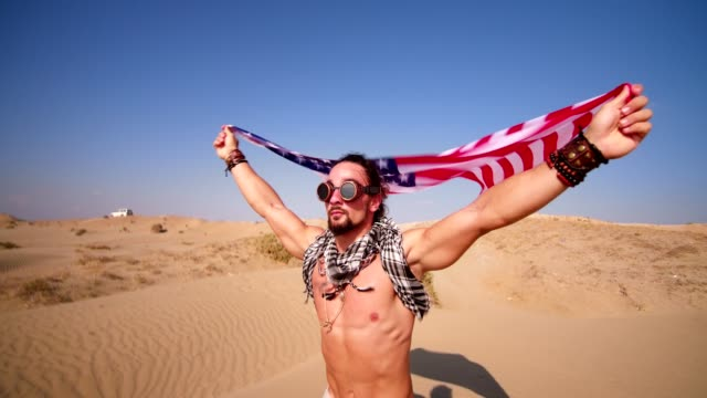 Man with steampunk goggles and american flag running in desert video