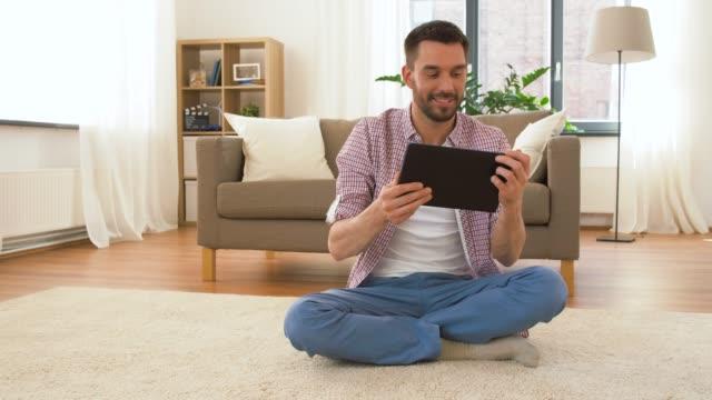 man with tablet computer meditating at home - vídeo