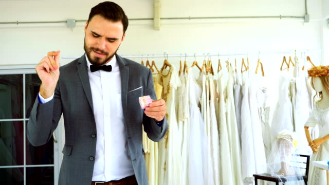 Man with the ring box is dancing and singing happily in the wedding dress shop