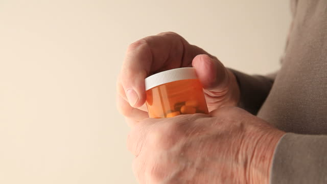 Man with tremor tries to open pills Senior with a disability cannot open his prescription medicine pill bottle stock videos & royalty-free footage