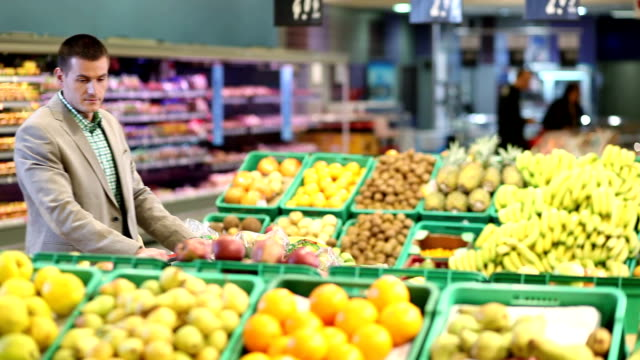 Man With Trolley By Fruit Counter In Supermarket video