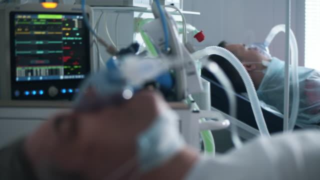 stockvideo's en b-roll-footage met een mens met ventilator die in klinische afdeling tijdens coronaviruspandemie ligt. - ventilator bed