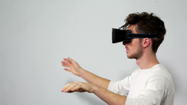 Man with VR headset enters a virtual reality world and interacts with the environment video