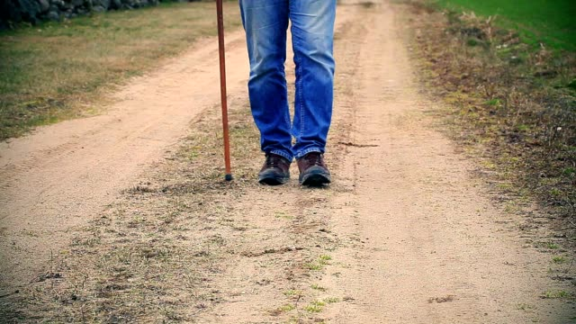Man with walking stick on the road Man with walking stick on the road crutch stock videos & royalty-free footage