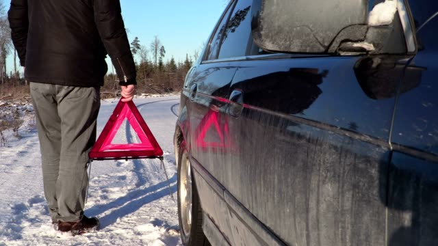 Man with warning triangle near car on the road in winter video