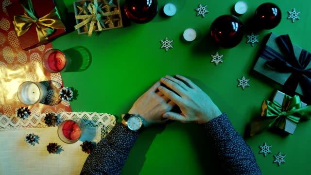 クロマキーと新年のテーブルに座って彼の手で時計を持つ男 ビデオ