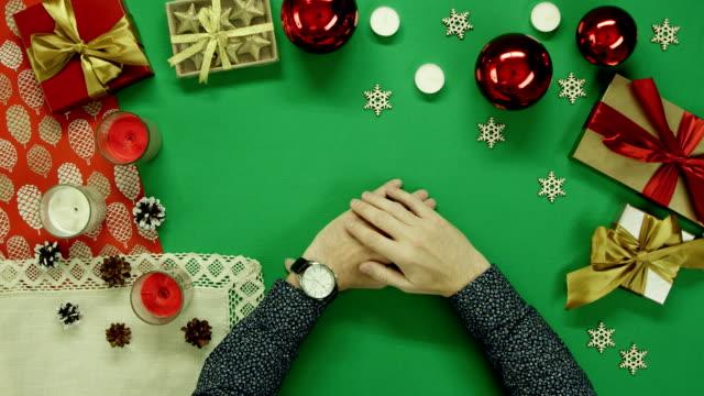 クロマキーでクリスマスのテーブルに座って彼の手で時計を持つ男 ビデオ